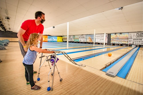 father with disabled girl bowling