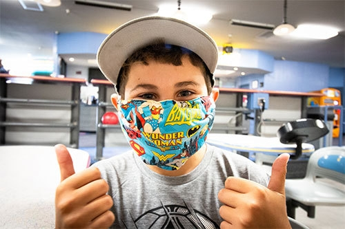 masked boy with thumbs up